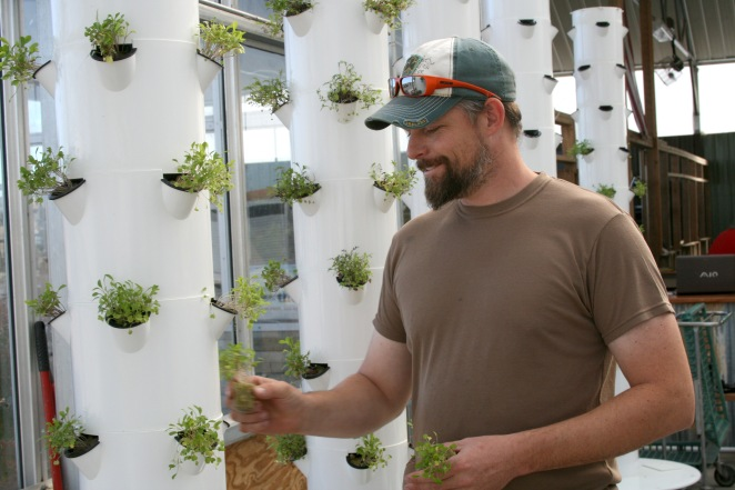 Evan Premer, a 15-year veteran of the Army National Guard, grows food in a greenhouse for his business, Dirtless Farm, in Colorado. Becoming a farmer has helped Premer manage his PTSD. (Photo by Cole Allen).